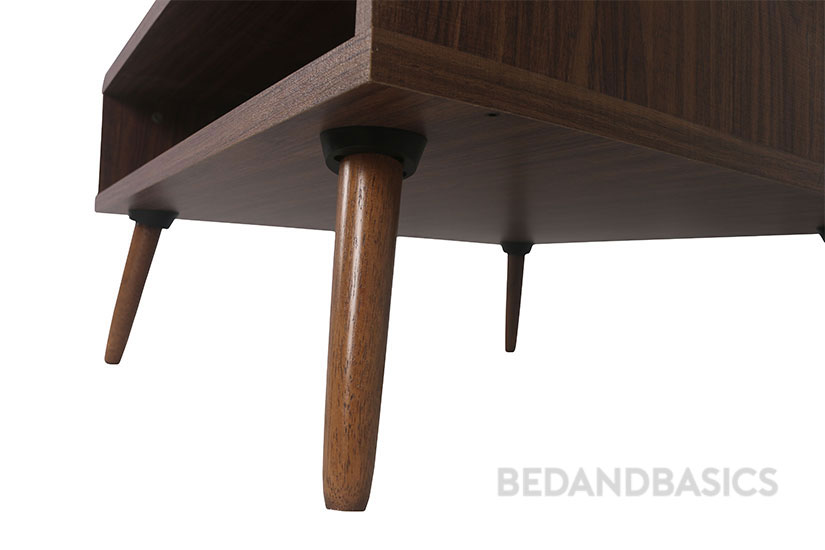 The coffee table is supported by round tapered wooden legs.