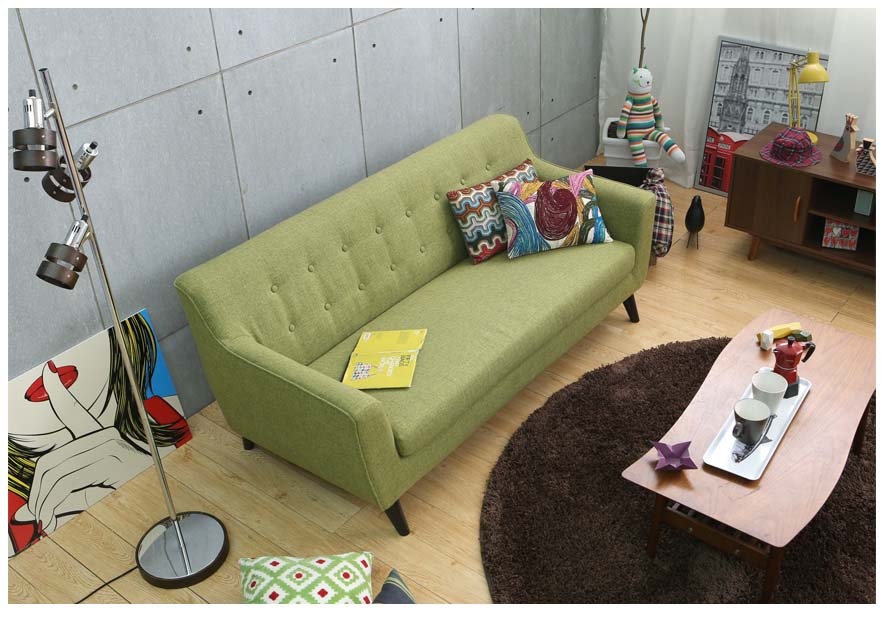 The Alba sofa green in a modern living room with industrial style wall.