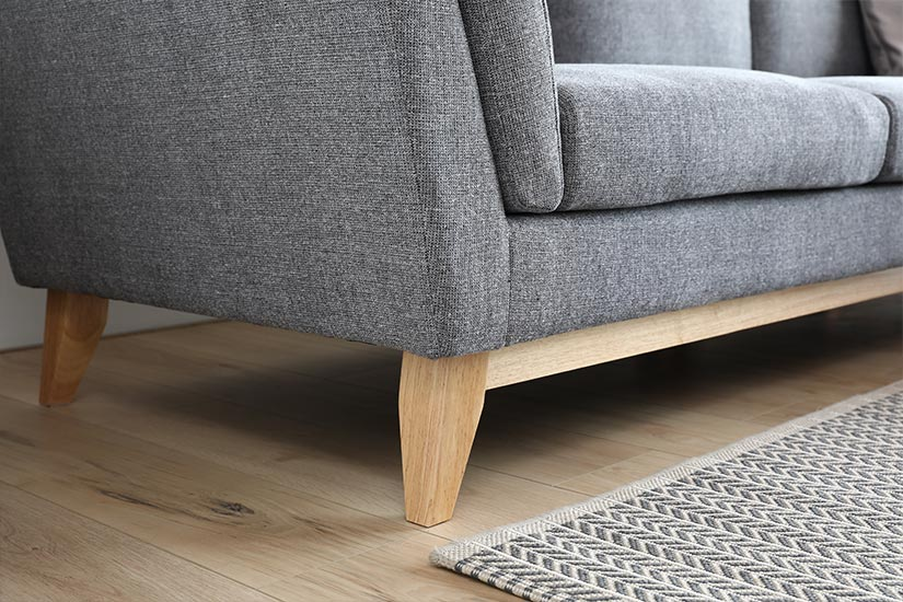 The legs' angular edges complement the straight silhouette of the sofa while creating contrast with its wood texture.