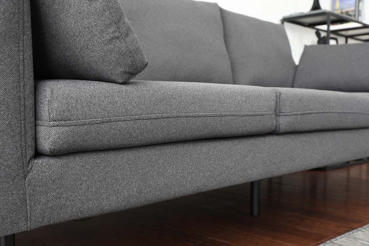 The texture pattern of the Charcoal Grey fabric has greater contrasts which creates a grain-like effect on the sofa.