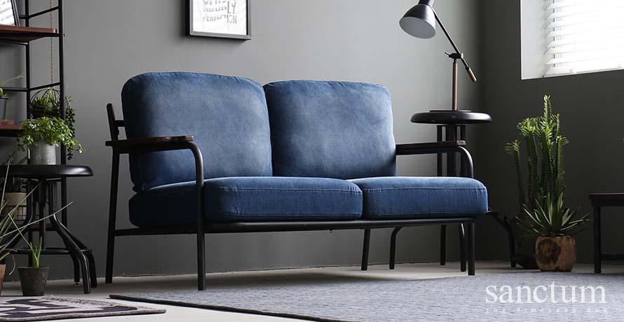 denim blue fabric sofa infront of a rug