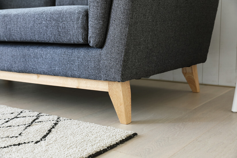 Solid Hevea wooden angular legs. Pale earthy tones. Woodgrain texture that contrast with the sofa's design.