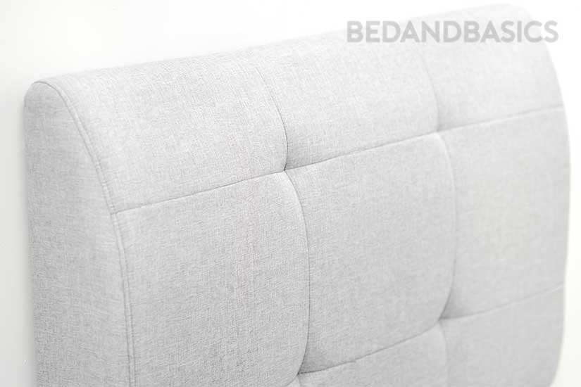 The biscuit-tufted backrest adds dimensionality to the headboard's design.