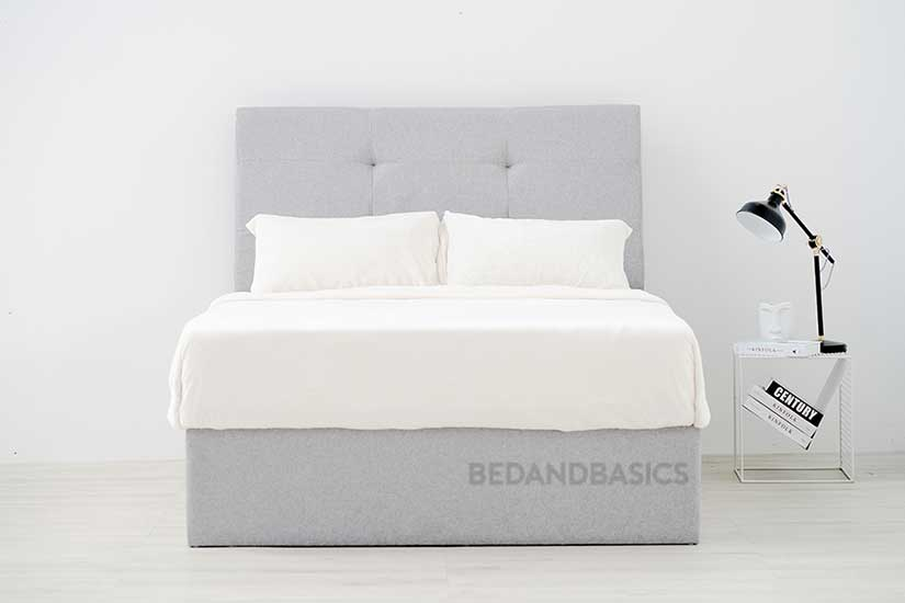 The HOLMVAM is an understated bed frame of textured upholstery and buttoned tuftings.