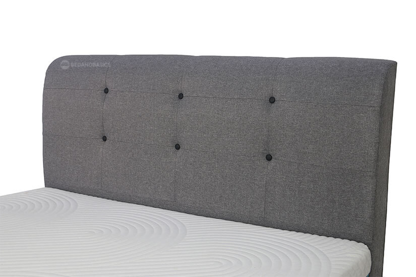 The headboard is detailed with black buttons for a more luxurious tufted look.